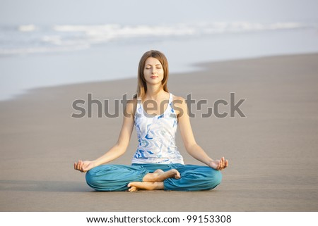 Young beautiful woman sitting in meditation pose on the beach - stock photo