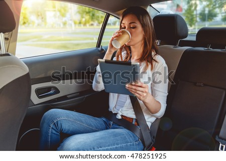 Young, beautiful woman sitting in the back seat of the car with a tablet in hand and drinking coffee
