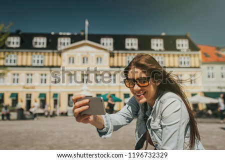 Young beautiful woman sitting in the city center taking a self portrait with her phone.