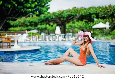 Young beautiful woman sitting near swimming pool