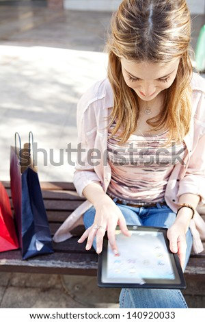 Young beautiful woman sitting on a bench in a city center with her shopping bags during a sunny day, using a digital tablet and smiling.