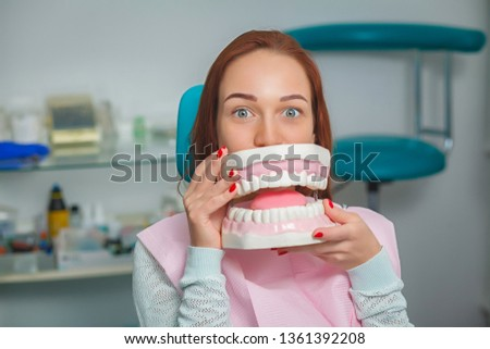 Young beautiful woman sitting on a dental chair and holding a plastic denture in a box. Funny photo.