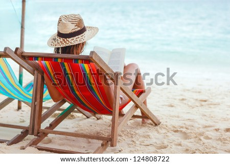 Young beautiful woman sitting on beach reading a book #124808722