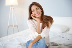 Young beautiful woman sitting on bed at home