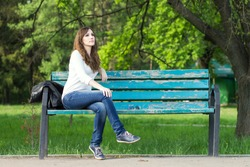 Young beautiful woman sitting on bench in park. Pretty girl at outdoors on summer day. Nature environment background.