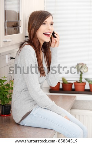 Young beautiful woman sitting on kitchen counter and talking by moibile phone