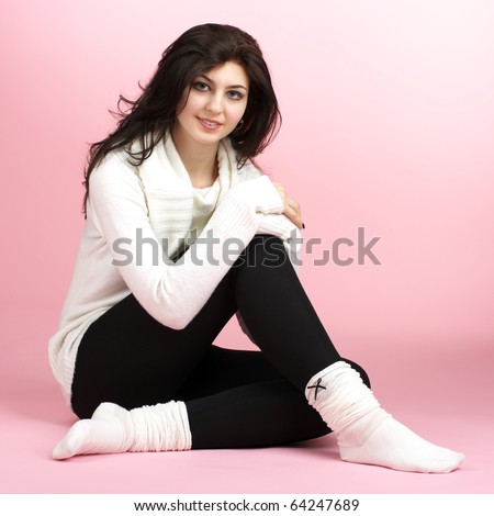 Young beautiful woman sitting on the floor over pink background