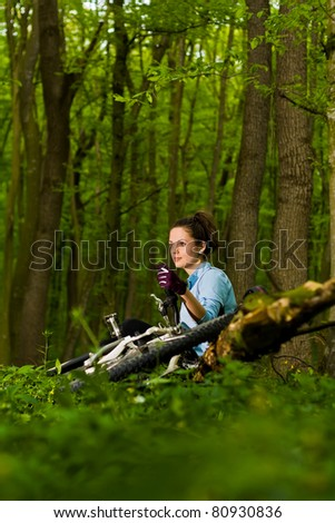young, beautiful woman sitting with bicycle