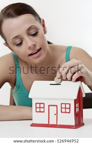 young beautiful woman sitting with  model house piggy bank,  real estate concept.