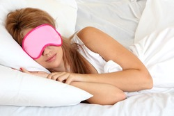young beautiful woman sleeping in bed with eye mask
