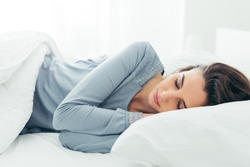 Young beautiful woman sleeping in her bed and relaxing in the morning