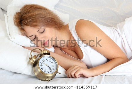 young beautiful woman sleeping on bed with alarm clock in bedroom