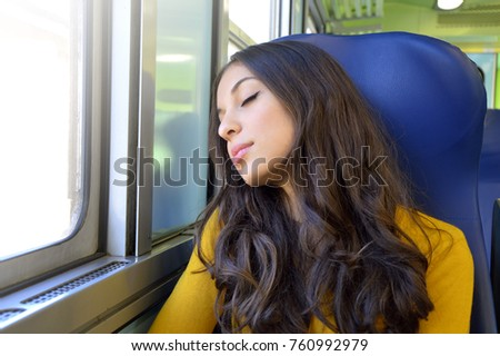 Young beautiful woman sleeping sitting in the train. Train passenger traveling sitting in a seat and sleeping.