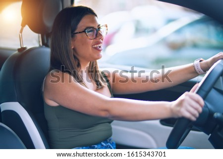Young beautiful woman smiling happy  and confident. Sitting with smile on face driving a car