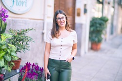 Young beautiful woman smiling happy and confident. Standing with smile on face at the town street
