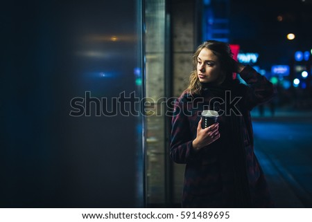 Young beautiful woman standing downtown at night with a coffee to go.