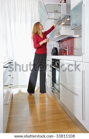 young beautiful woman standing in modern kitchen interior