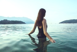 Young beautiful woman standing in the water.