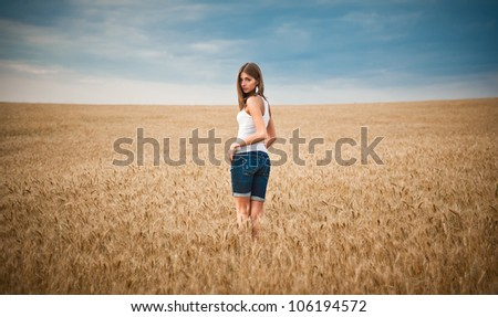 Young beautiful woman standing in wheat field under blue sky, looking straight to the camera