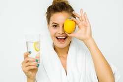 young beautiful woman standing on a white wall in bath towel playing with a lemon, water with lemon for healthy concept