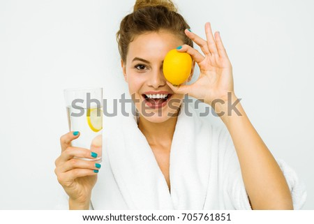 young beautiful woman standing on a white wall in bath towel playing with a lemon, water with lemon for healthy concept #705761851