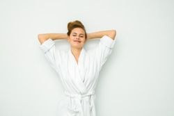 young beautiful woman standing on a white wall in bath towel with fresh water with lemon for healthy