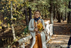 Young beautiful woman standing on the bridge made of birch logs, in autumn park, holding a bunch of yellow maple leaves