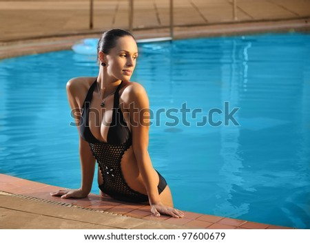 Young beautiful woman standing on the side of swimming pool