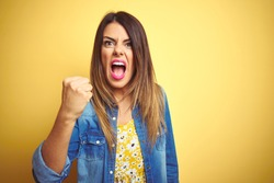 Young beautiful woman standing over yellow isolated background angry and mad raising fist frustrated and furious while shouting with anger. Rage and aggressive concept.