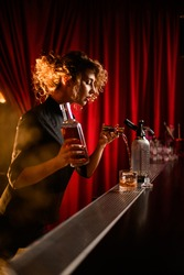 young beautiful woman stands behind the bar holding bottle of liquor in her hand and pours drink from jigger into glass