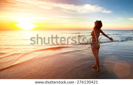 Young beautiful woman stands towards the sun on Sea beach during a amazing sunset. #276130421