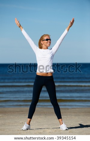 Young beautiful woman stretching on the beach - stock photo