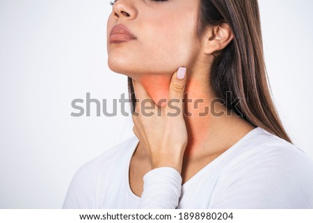 Young beautiful woman suffering from pain in throat, touching inflamed zone on her neck, cropped, empty space, sore throat Foto stock ©