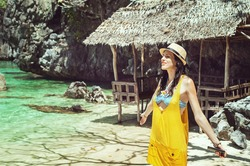 Young beautiful woman takes sunbaths on the seashore on an island in the Philippines Beautiful girl in beachwear enjoys the sun and the sea on the background of rocks,concept of summer holidays at sea