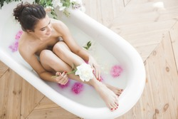 Young beautiful woman taking bath with flowers and milk