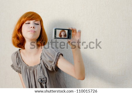 Young beautiful woman taking picture of herself, selfshot or selfy on mobile touch phone portrait