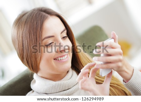 Young beautiful woman text messaging