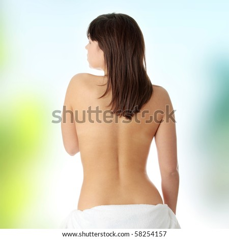 Young beautiful woman topless, in towel, view from back