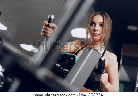Young beautiful woman training her arms in a gym apparatus Stock foto ©