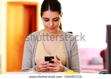 Young beautiful woman typing on smartphone at home