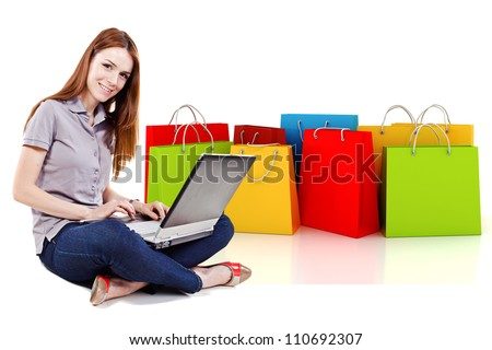 young beautiful woman using a laptop for online shopping with 3d shopping bags in the background - stock photo