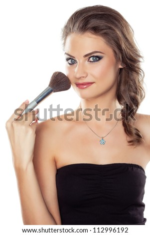 Young beautiful woman using a make-up brush, isolated on white