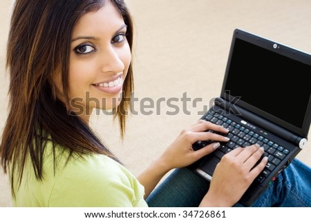 young beautiful woman using laptop on bedroom floor