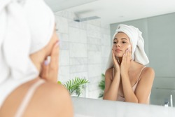Young beautiful woman using skin face cream moisturizing lotion after taking bath. Pretty attractive girl wearing towel on head standing front of mirror in home bathroom. Daily hygiene and skincare