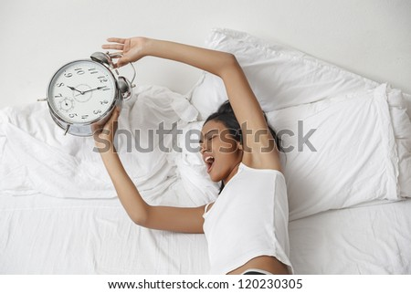 Young beautiful woman waking up in the morning. Alarm clock ringing.