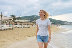 Young beautiful woman walking along evening beach, female teenager in denim shorts T-shirt restng on seashore, vacation weekend, beautiful sea natural landscape, active lifestyle