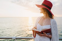 young beautiful woman walking by the sea, reading travel diary book, morning sunrise, romantic mood, red hat, thinking of memories, bohemian style outfit