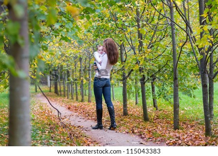 Young beautiful woman walking with her baby in a park