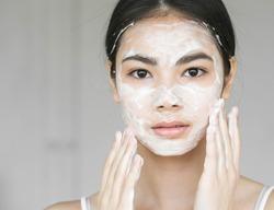 Young beautiful woman washing her face with soap. Studio shot.