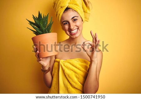 Young beautiful woman wearing a towel holding aloe vera pot over yellow isolated background doing ok sign with fingers, excellent symbol
